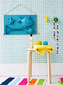 Hand-crafted arrangement of sand-pit moulds decorating bathroom wall