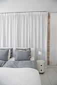 White bedroom with grey bed linen on double bed and floor-length curtains at head