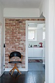 Retro chair with black leather cover against brick wall in hallway with view of white kitchen counter through open door