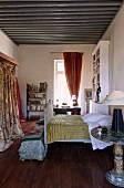 Antikes Schlittenbett mit Tagesdecke und Schrank mit gemustertem Vorhang in mediterranem Ambiente