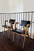 Retro Stühle aus hellem Holzgestell vor Metall-Treppengeländer