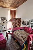 Gemütliches Bett mit folkloristischer Tagesdecke, Kissen in pinkfarbenen Bezügen in eklektischem Ambiente