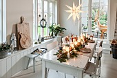 Christmas table decorated with fir branches and illuminated stars in front of French windows with view of fake reindeer