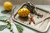 Lemon studded with cloves, open jar of cloves and cinnamon sticks on vintage tray
