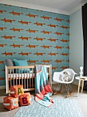 Dog-patterned wallpaper, cot, cushion building blocks on floor and classic rocking chair in nursery