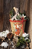 Papier mâché plant pot decorated with festive vintage scrapbook pictures