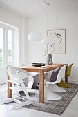 Wooden table and designer chairs in white dining room