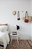 Stacked books on white wooden chair with hat on backrest below bags and hat hung on wall-mounted pegs in bedroom
