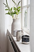 Vase of flowering twigs and various ceramic vessels on windowsill