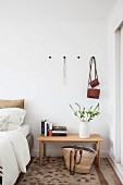 Stack of books and vase of flowering branches on wooden bedside table below bags hanging from coat pegs