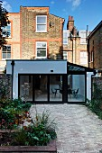 Garden of traditional, English terraced house with paved area and view of white modern extension