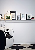 Various pictures stood on DIY shelf with white-painted moulded trim