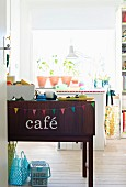 Sideboard decorated with bunting and lettering spelling 'café' in front of plants on windowsill in girl's bedroom