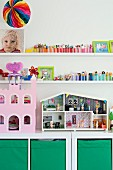 Dolls' house and pink dolls' castle on white cabinet with green storage boxes below collection of toys on white shelves