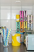 Colourful drinking straws, yellow tin and stack of colourful boxes of tea on kitchen worksurface