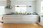 White kitchen counter with bar handles below window in tiled wall with house plants on windowsill