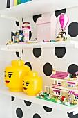 Shelves of toys on polka-dot wall