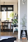 House plant on black metal stool next to open doorway with view of bistro-style dining area below window