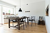 Rustic wooden table and designer chairs in minimalist dining room
