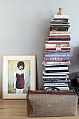 Gerahmtes Bild mit Frauenmotiv neben Bücherstapel und Vintage Arzttasche auf Parkettboden