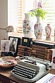 Vintage typewriter and ceramic bowl in front of stacked antiquarian books on table below window with vases on sill