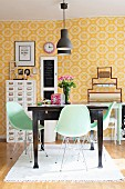 Pastel-green shell chairs around dark wooden table in dining room with yellow and white patterned wallpaper
