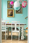 White wooden chairs and vintage table in decorated dining room with gilt-framed floral pictures on blue wall