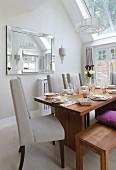 Elegant gedeckter Holztisch mit Sitzbank und hellgrauen Polsterstühlen, Wandspiegel und Oberlicht