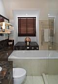 Dunkelfarbene Marmor-Waschtischplatte mit Ablageflächen, weiße Badewanne und Glas-Duschabtrennung im Bad