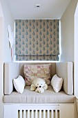 Cushions and soft toys on comfortable seat in dormer window seat with patterned Roman blind
