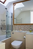 Bathroom with toilet against pale beige half-height wall below mosaic tiles; bathtub with glass screen to one side