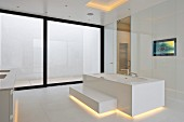 Designer bathtub with step and indirect lighting in minimalist, white, designer bathroom