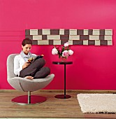 DIY wall hanging made from leather remnants on hot pink wall; woman sitting on chair reading