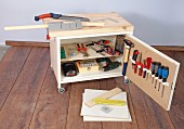 Small workbench on castors with wooden top and cupboard