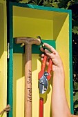 Secateurs and spade hanging in DIY garden cupboard