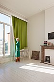 Woman standing by window with green curtain in period apartment with white wooden floor