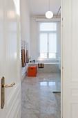 View through open door into modern marble bathroom in period apartment