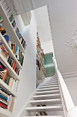 View up staircase lined by floor-to-ceiling bookcases