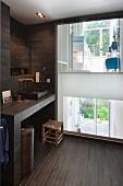 Dunkel gefliestes Bad mit Lichtfenster, Blick in Wohnung und Garten
