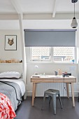Wooden desk and classic grey metal stool below window with roller blind in Scandinavian-style, teenager's bedroom