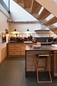Kitchen with wooden fronts and staircase in industrial loft apartment