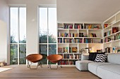 Retro leather shell chairs in front of tall windows, bookcases and grey sofa in living room