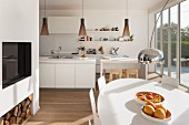 Fruit bowl on white oval dining table in front of open-plan kitchen with glass wall