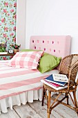 Bed with pink, button-tufted, DIY headboard in feminine bedroom