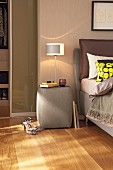 Table lamp on grey upholstered bedside table with glass top