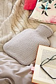 Hot-water bottle with pale grey knitted cover, blanket and book on bed