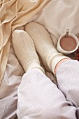 Feet in warm bed socks and a cup of cocoa in bed