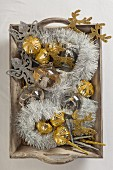 Silver and gold Christmas decorations on wooden tray