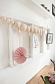 String of wooden beads and pink paper pendant on white wooden frame