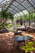 Luxuriant planting in greenhouse with central stone table and folding garden table